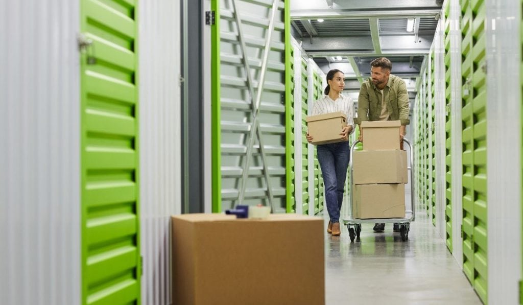 couple in a storage facility bringing some boxes of different stuff to store