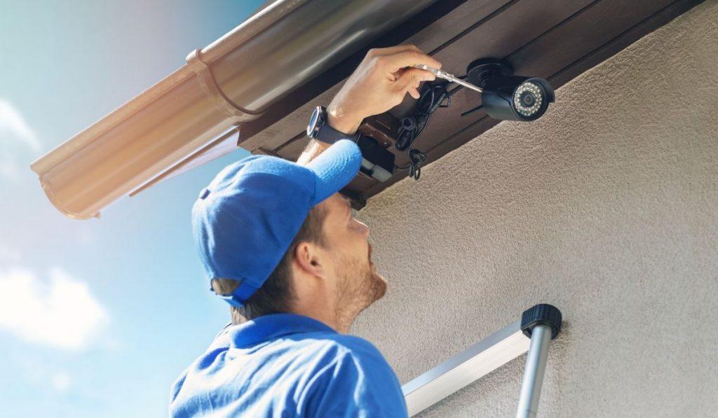 man installing a security camera at a storage facility