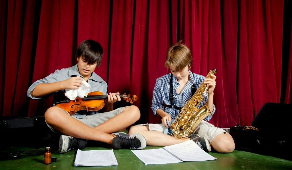 two boys cleaning their musical instruments